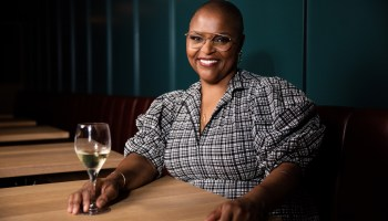 Chef Tanya Holland sits at a booth with a glass of wine at Brown Sugar Kitchen in Oakland. Photo: Smeeta Mahanti