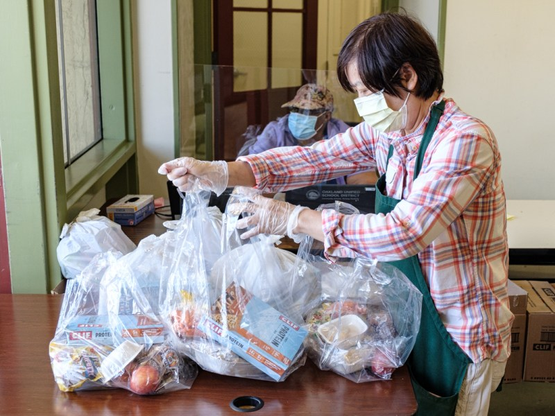 Yu Chem Li packing bags of food for OUSD families