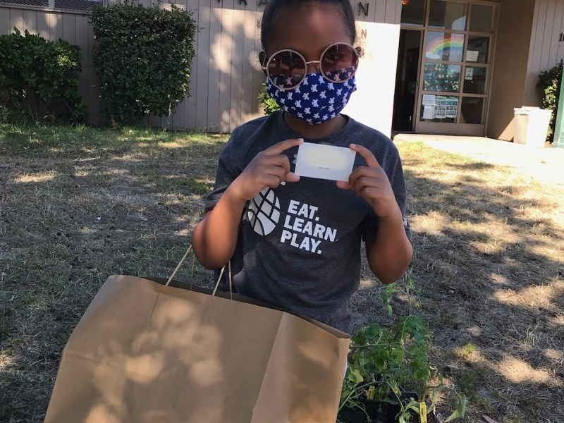 A Town Camp attendee at the Franklin Center holds a bag of meals from Kitchens Around the World to share with her family. Photo courtesy Oakland Parks, Recreation & Youth Development