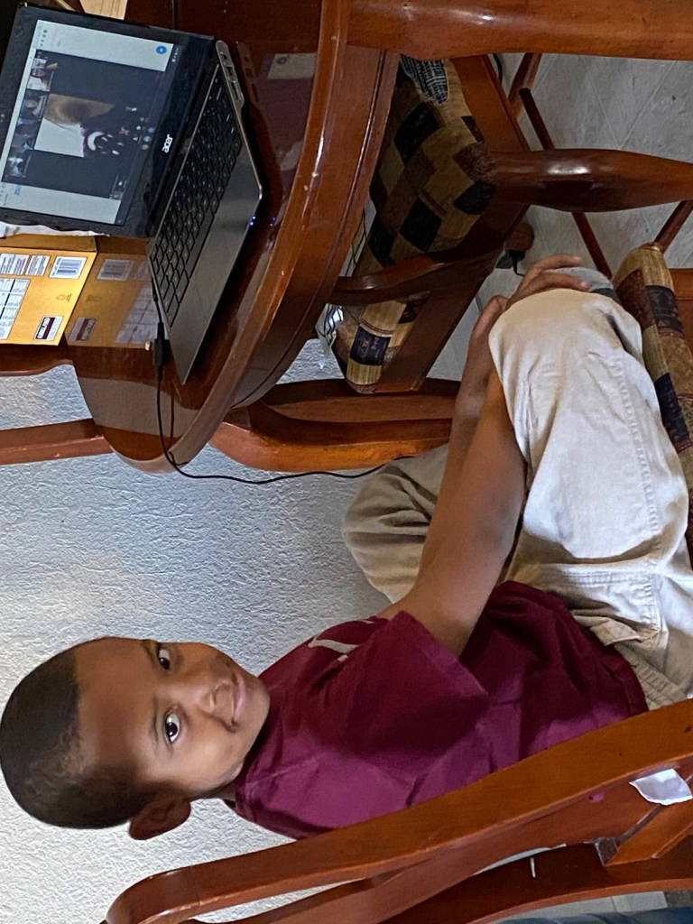 boy sitting at table in front of computer
