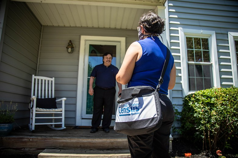 Woman with a census tote bag has back to camera. Smiling man stands on his porch talking to her.