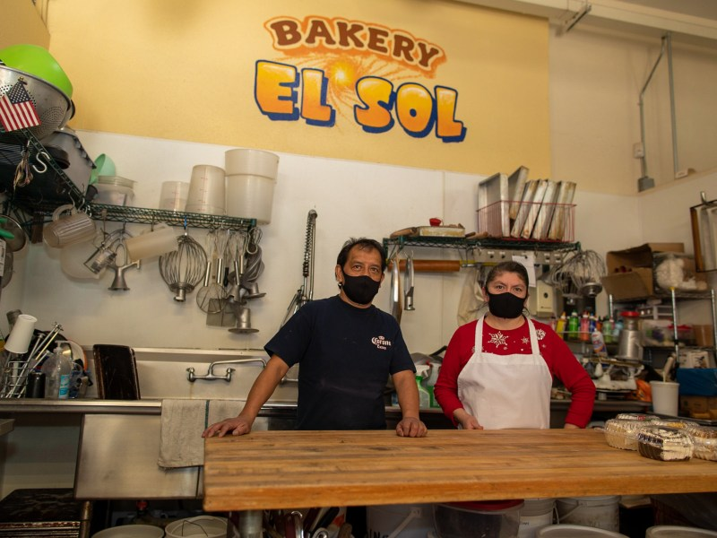 Owners of Bakery El Sol in front of signage