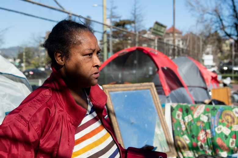 close up of woman, with sober expression, staring. tent in background