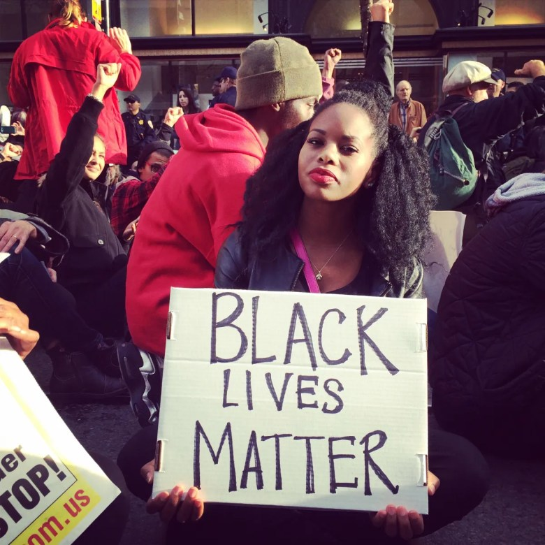 Aishatu Yusuf, director of innovation programs at Impact Justice, holds a Black Lives Matter sign in Oakland, Caliifornia.