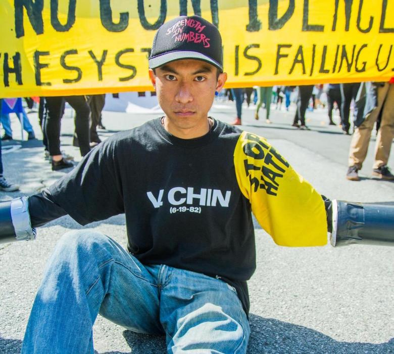 Man in 30s sitting on ground with arms outstreched/chained; protest sign in background