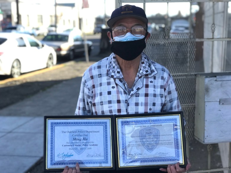 Ming Ho, 74, outside his home in Eastlake, holding certificates he was awarded by the Oakland Police Department for his volunteer public safety work.