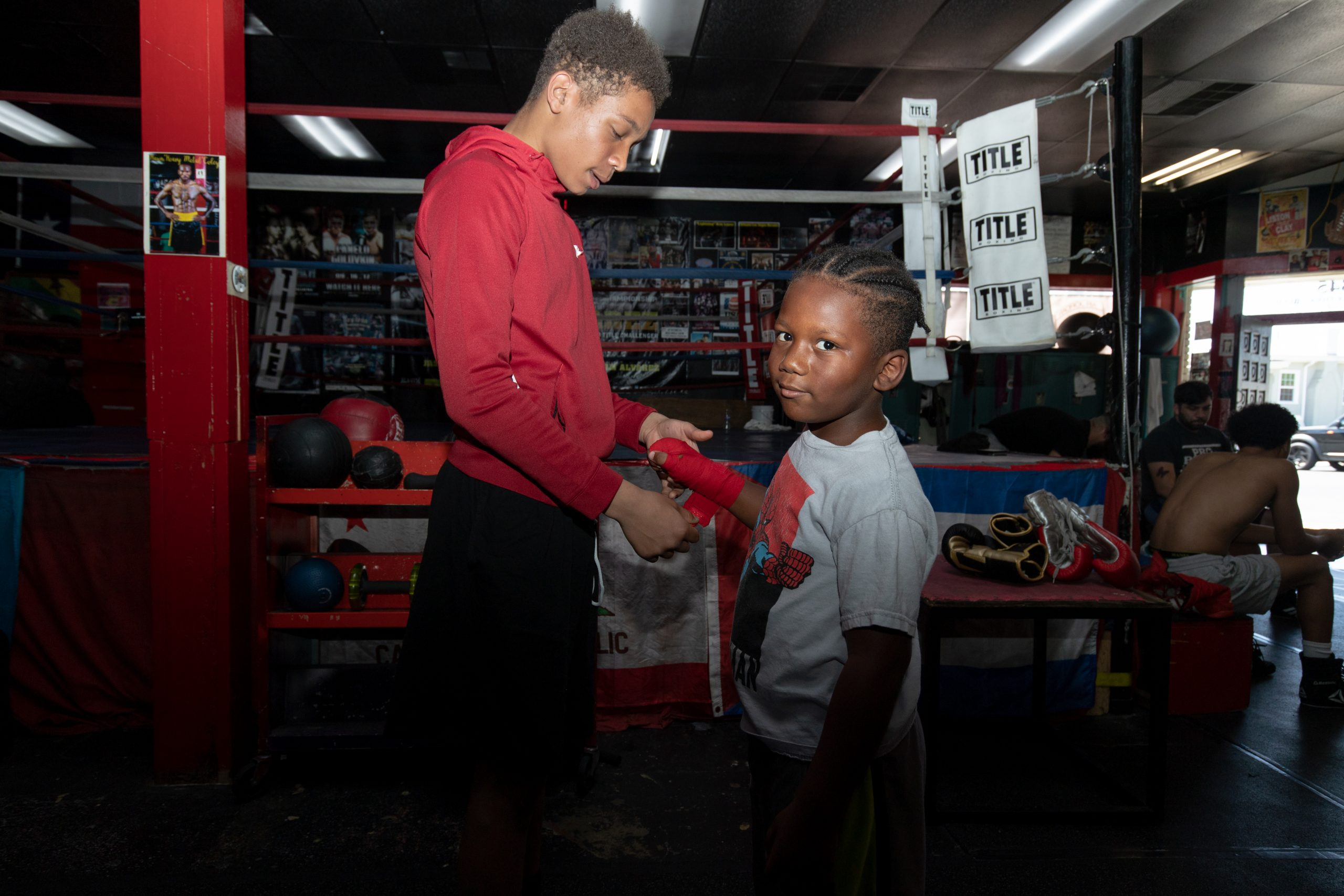 Youth help each other put on boxing gloves before they practice together.