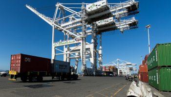 A big-rig truck hauls a shipping container at Howard Terminal.