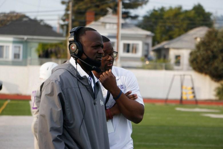 Castlemont High head football coach Ed Washington and secondary coach John McLeod watch their team play against McClymonds High on April 10, 2021.
