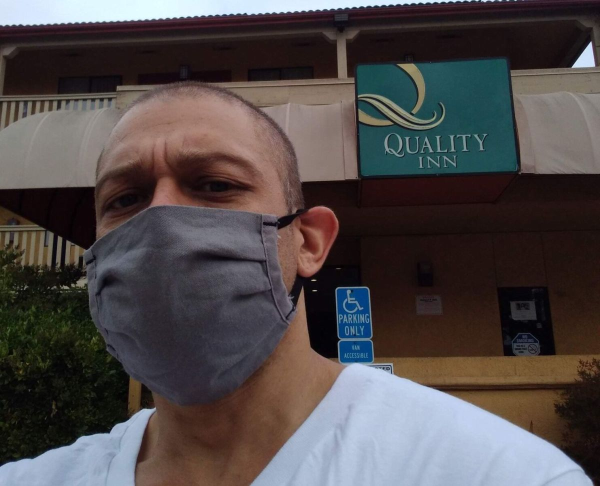 The author, Kerry Rudd, takes a selfie in front of a Quality Inn in Oakland that is being used to quarantine people who've tested positive for COVID-19.
