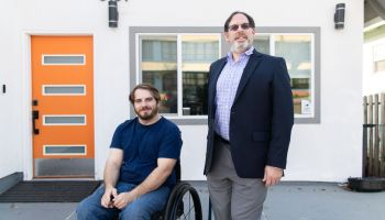 Thirty-something white man in a wheelchair poses next to a slightly older white man who's wearing a suit and standing with a cane. They're in front of a house with an orange door.