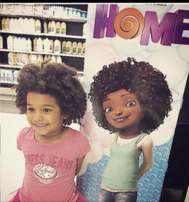 A young girl poses in front of a poster for the movie