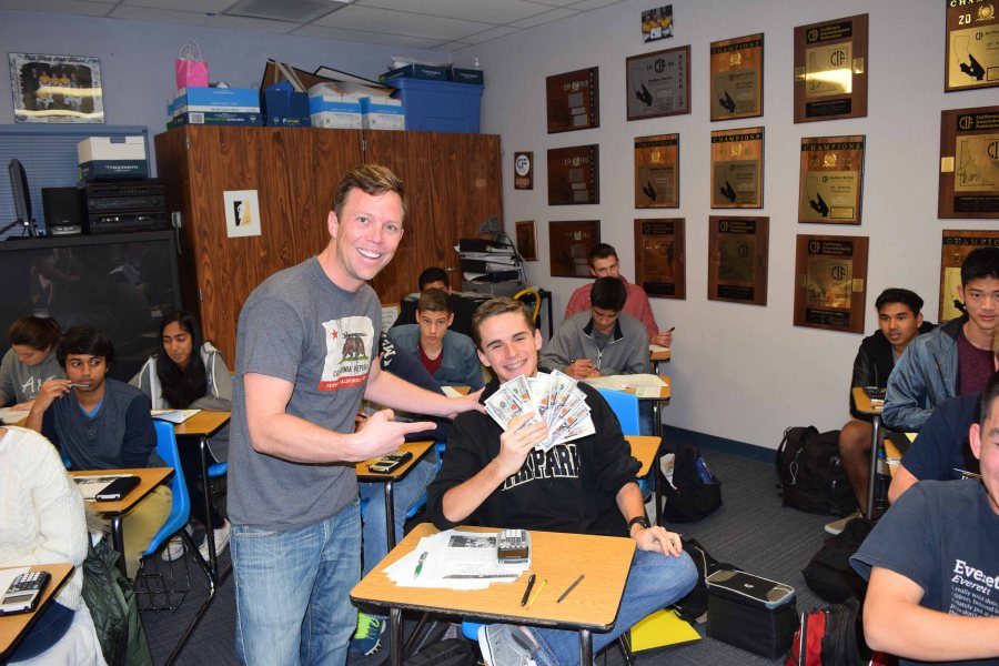 Senior+Justin+Haddox+holds+up+his+%E2%80%9CCook+Bucks%E2%80%9D+%E2%80%94+economics+teacher+D.J.+Cook%E2%80%99s+incentive+to+encourage+students+to+participate+during+class+discussions.+Cook+utilizes+a+combination+of+economics+teacher+Kevin+Smith%E2%80%99s+syllabus+and+his+own+%28Anastasia+Greer%2FTalon%29.