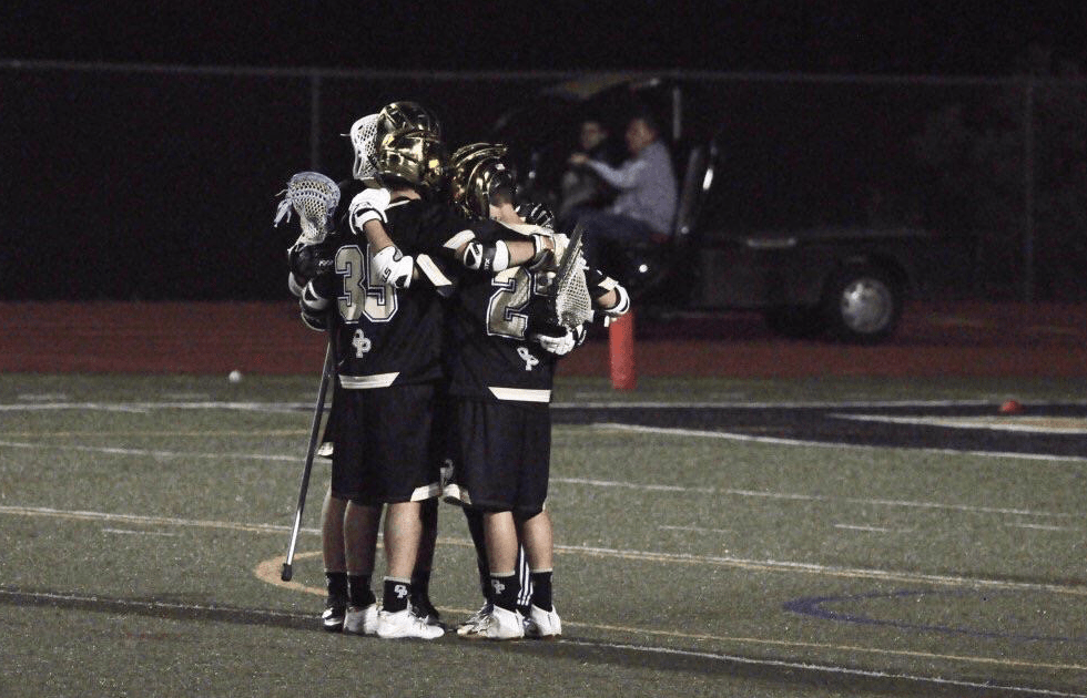 Freshman Joey Rosen and seniors Brandon Byer and Ryan Goodnogh embrace during a lacrosse game. This season, the team has had to cope with multiple injuries, including three injured goalies (Photograph reprinted with permission from Tarik Ergin).