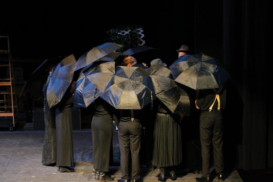 Student drama members huddle during a funeral in Our Town.