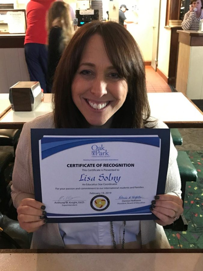 Lisa Solny poses with her certificate of recognition from OPUSD board members.