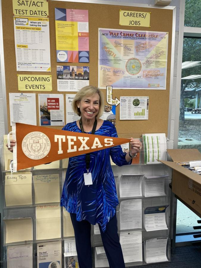 Paula Friedman holding the University of Texas at Austin college banner, the university is located in the city of her new home.