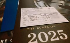 Anonymous vaccine card on top of a pile of acceptance letters from colleges that will require the COVID-19 vaccine for the fall of 2021