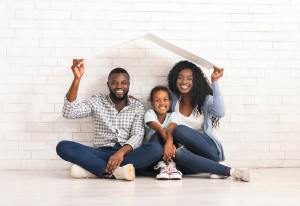 African American Family Sitting Under Roof Dreaming Of New Home