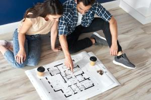 Couple looking at blueprint in new house
