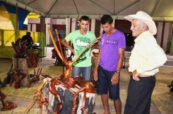 O público se encantou com o trabalho do escultor da floresta. O artista explica aos visitantes como cria suas peças