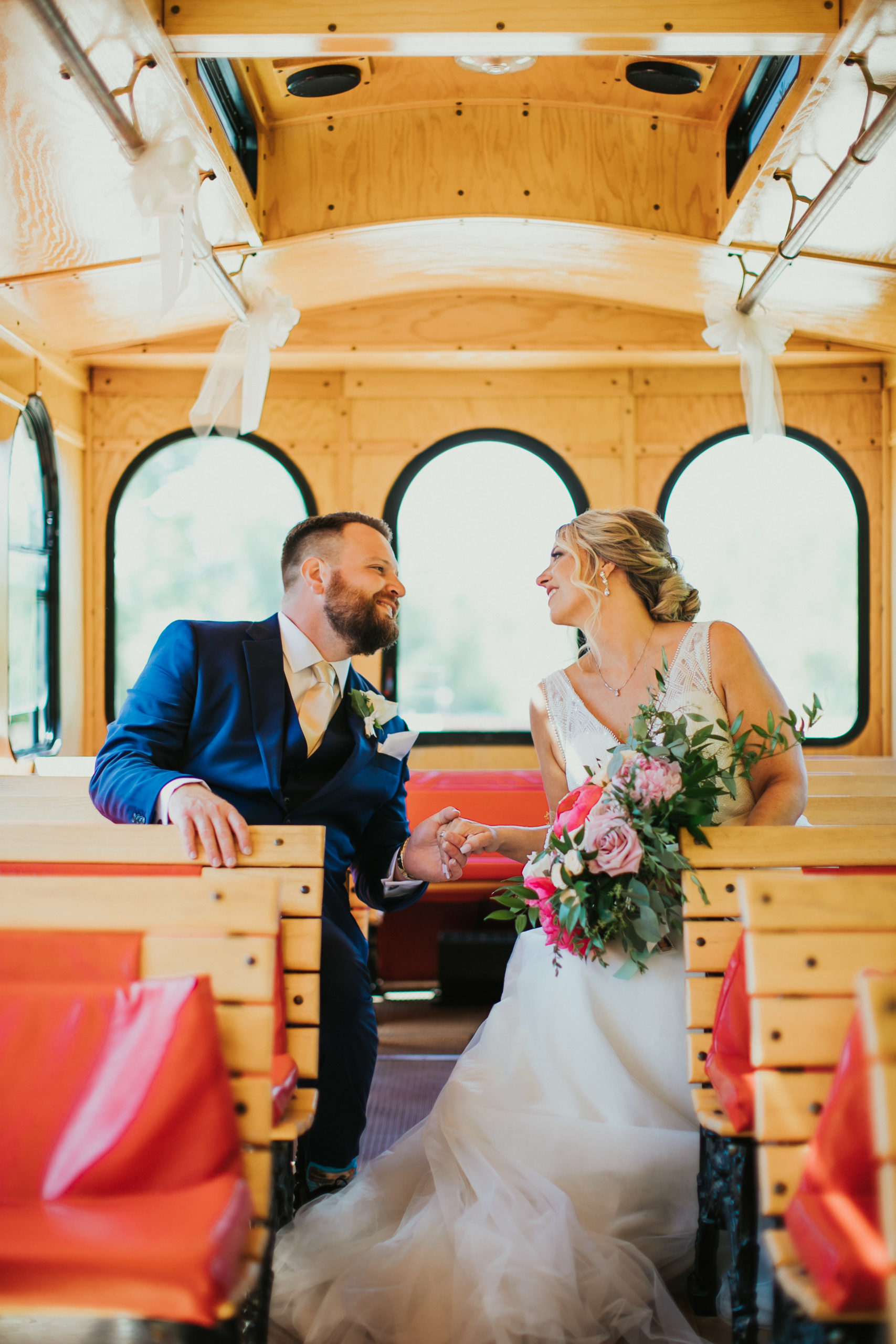 A bride and groom gaze at each other on a Door County Trolley
