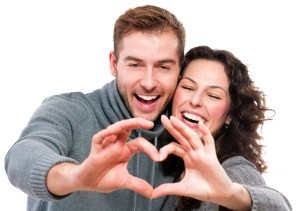 young man and woman smiling as they make a heart shape with their hands