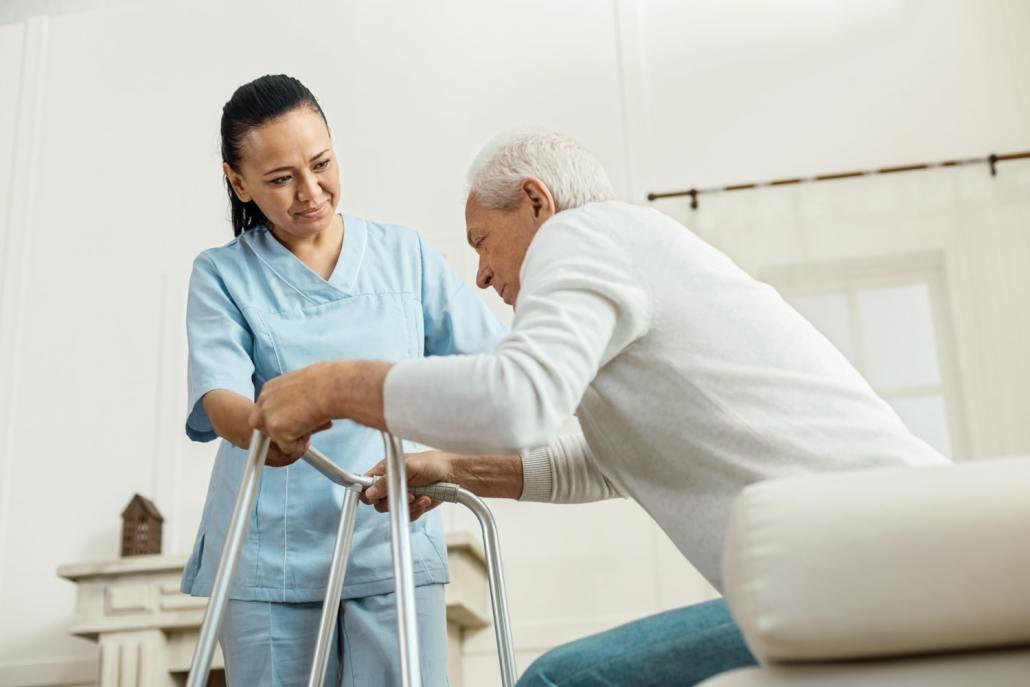 caregiver helping senior to stand