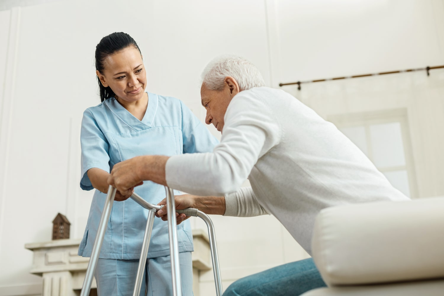 caregiver helping senior to stand