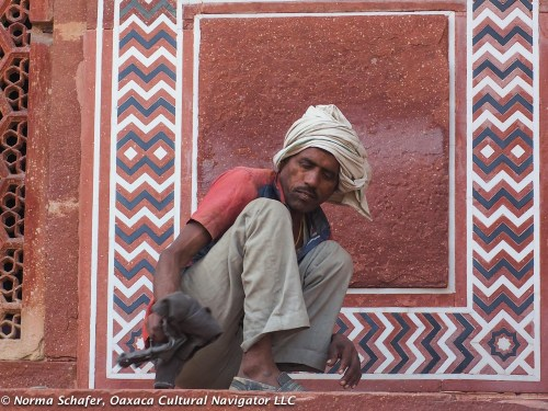 Worker uses damp rag to clean Taj Mahal exterior.
