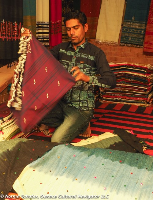 Artisan from Ahmedabad folds shawls inset with mirrors embroidered to silk.