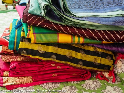 Stack of sari fabric, neatly folded and ready for hangers.
