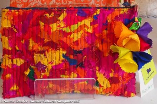 Trademark cloth flowers embellish zipper pulls on scrap fabric bag