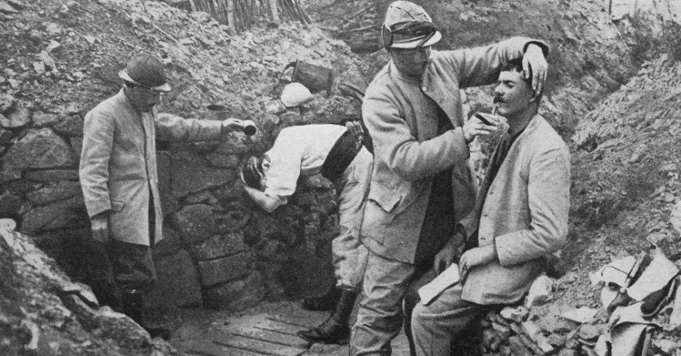 """Poilu é um termo informal e amigável utilizado para indicar membros da infantaria francesa da Primeira Guerra Mundial. A tradução literal é """"peludo"""". Soldados franceses ajudam os companheiros a fazer a barba e se lavar nas trincheiras da Primeira Guerra Mundial. A foto foi divulgada pelo museu francês Historial de Péronne."""