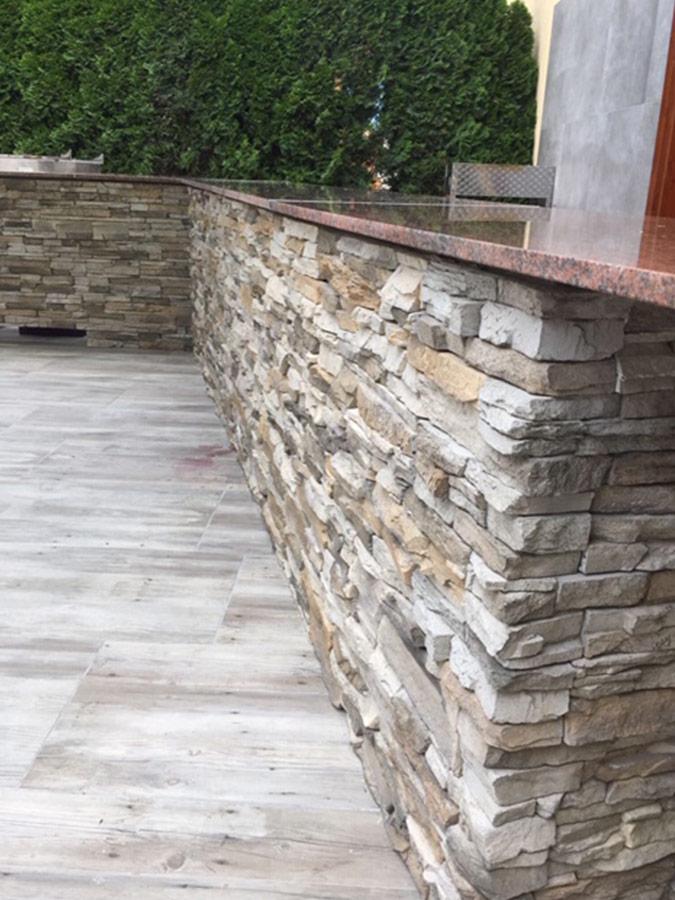 Holzfliesen und rustikale Steinmauer mit Wandverblender.