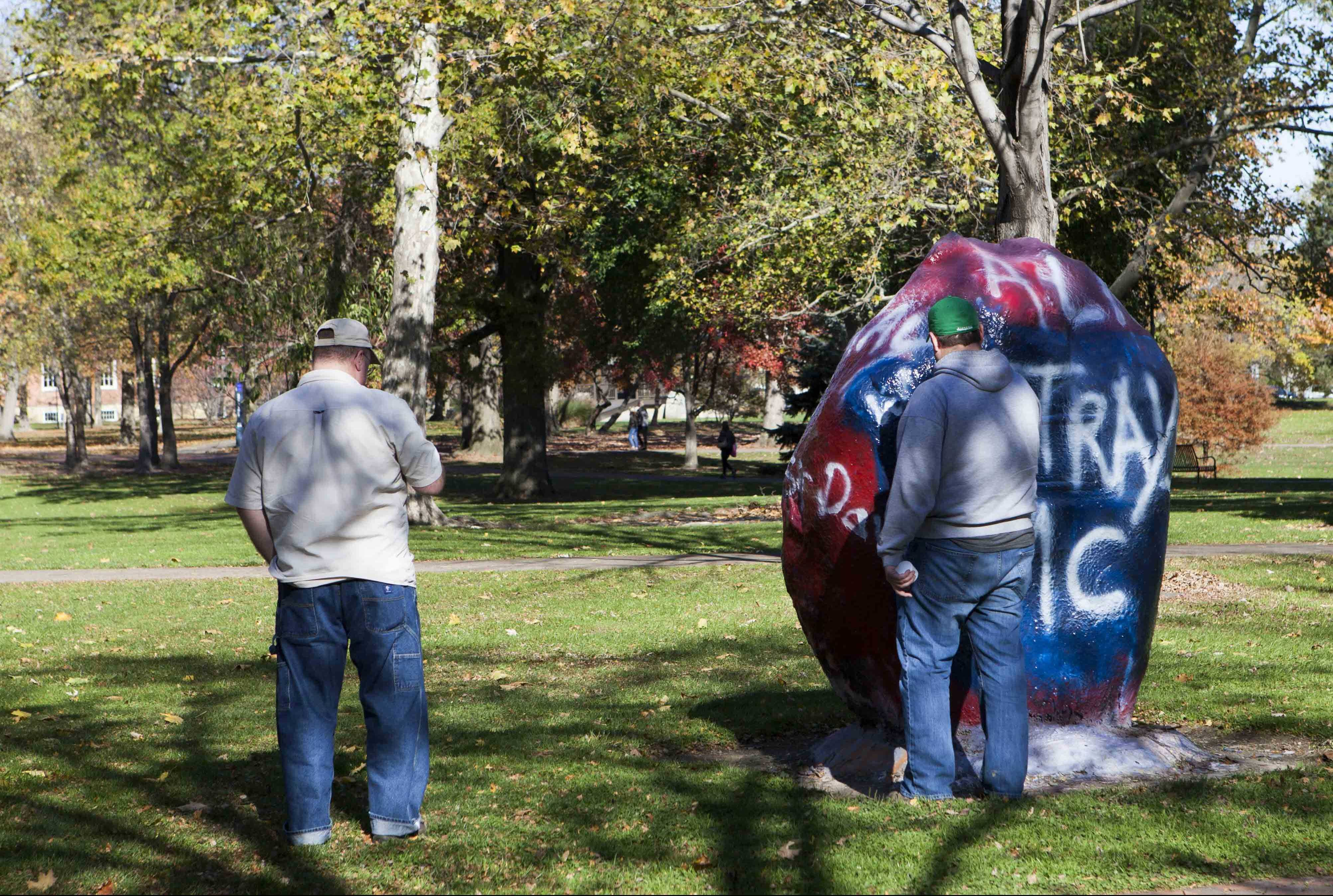 """Members of the biker club Strays Grafton write the group's name over a Tappan Square rock Saturday morning that had read """"Black Lives Matter."""" At least three different biker groups, including the Hell's Angels, came out to support Gibson's."""