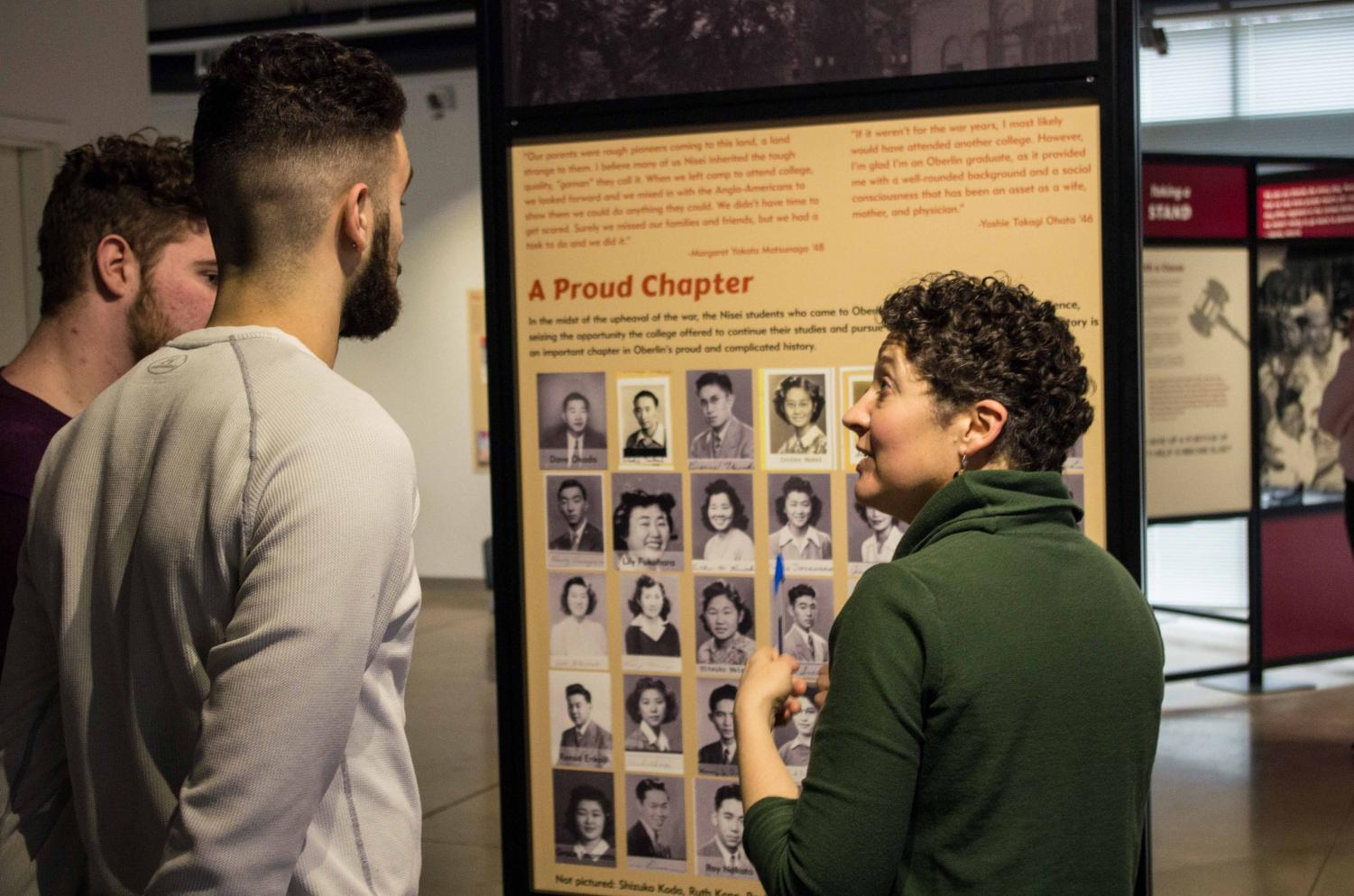 """Professor Renee Romano discusses the nationally-touring exhibit """"Courage and Compassion"""" with sophomores Justin Godfrey and Abe Kuhn."""