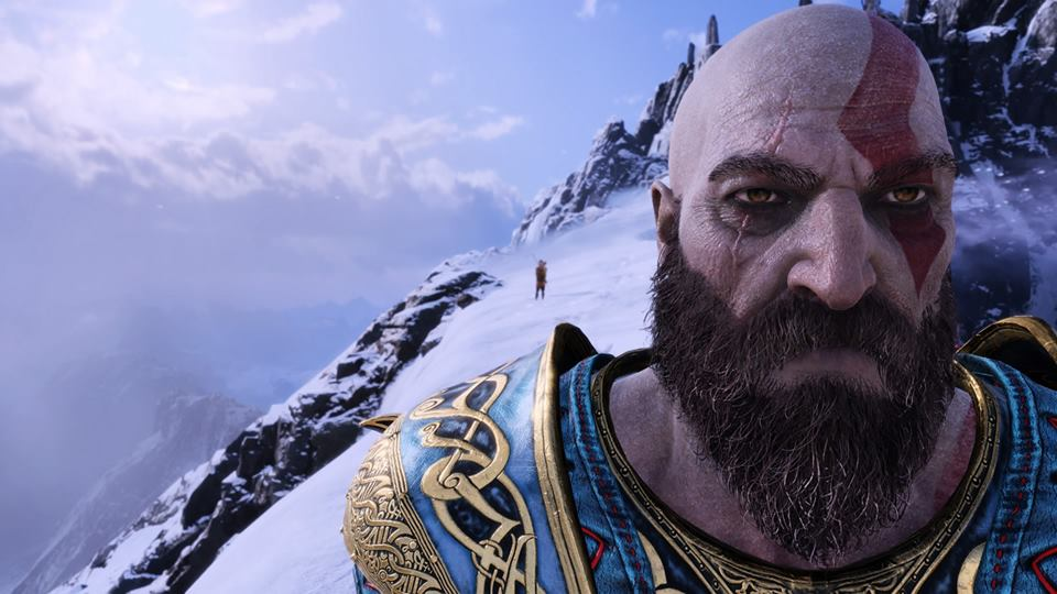 A stone-faced Kratos crosses the peak of a mountain with his son, Atreus, in Santa Monica Studio's PlayStation 4 masterpiece