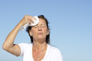 woman outside wiping her face with towel