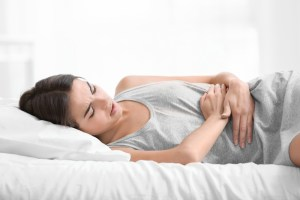 woman laying down experiencing menstrual pain