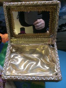 Un petit coffre a été doublé de tissu par dessus une couche de ouate synthltique, un miroir a été inséré dans le couvercle et des galons ont été utilisés pour la garniture. Une boîte a musique a été installée dans le coin en haut, à droite, sous le tissu