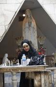 A Muslims woman lights candles at Virgin Mary Chaldean Church in Baghdad, Iraq. (AP Photo/Hadi Mizban)