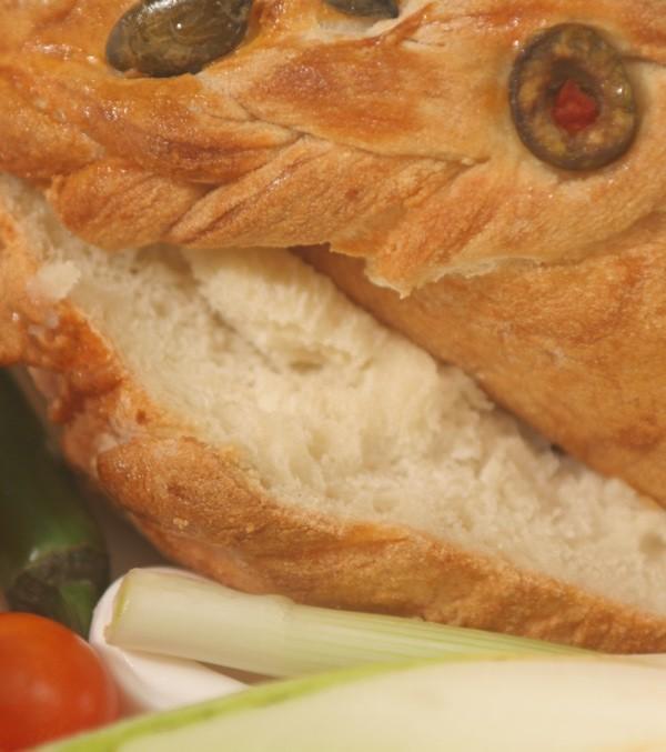 Tek načeta šunka u kruhu koju tek treba narezivati, ukrašena bučinim sjemenkama i rezanim maslinama (Snimio Igor Sitar / Acumen)