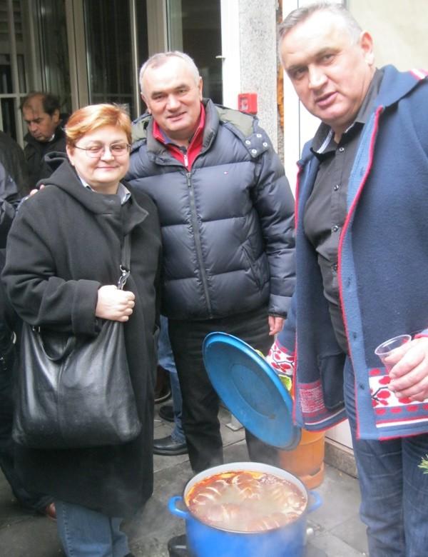 Božica Brkan, urednica Oblizeka, s braćom Galoviće, Tomislavom (u sredini) i Marijanom nad rajnglom u kojoj se kuha još jedna runda zasad još nedovoljno osušenih kulena (Snimio Miljenko Brezak / Acumen)