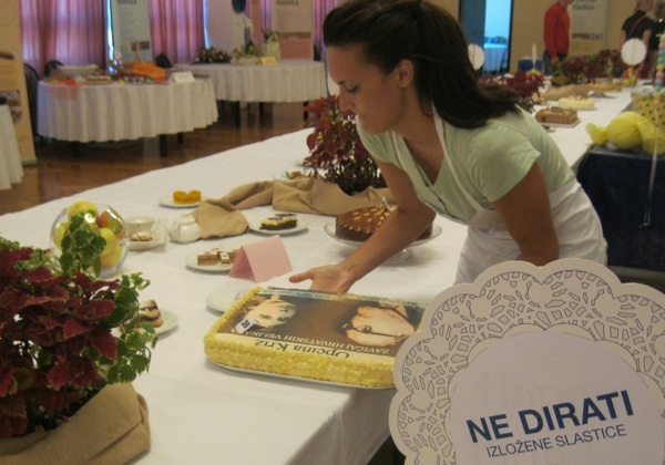 Postavljanje izložbe: torta s kriškim velikanima Josipom badalićem i Milkom trninom (Snimio Miljenko Brezak / Oblizeki)