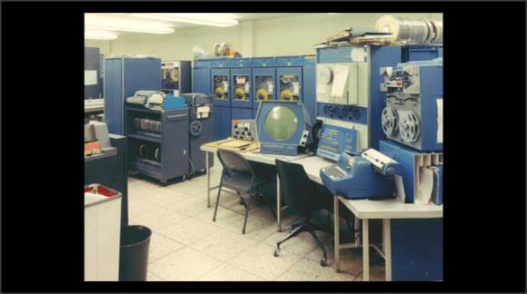 Foto del mismo ordenador, rodeado de armarios de periféricos