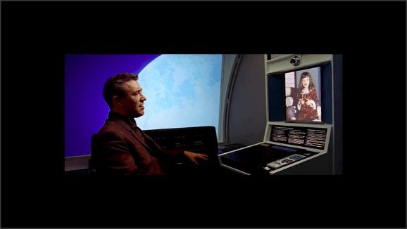 Captura de una película de ciencia ficción no determinada. Un hombre habla con una niña por videoconferencia