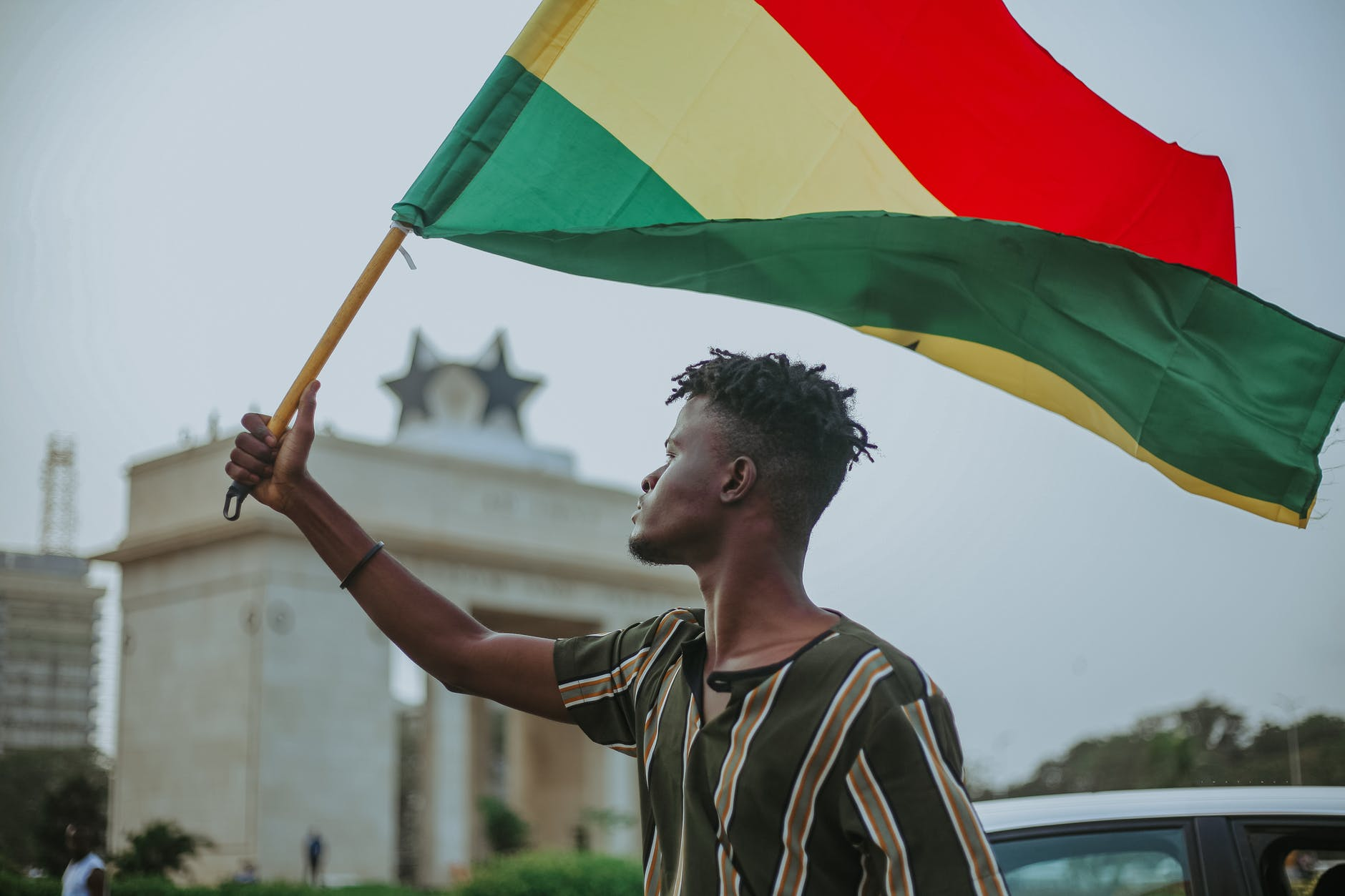 black man with flag of ghana on city street