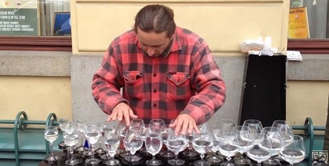Artista de rua tirando musica de copos de cristal