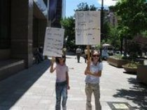 AP Photo: Pyper, 7, and Sadie Vance, 9, hold signs in downtown Salt Lake City
